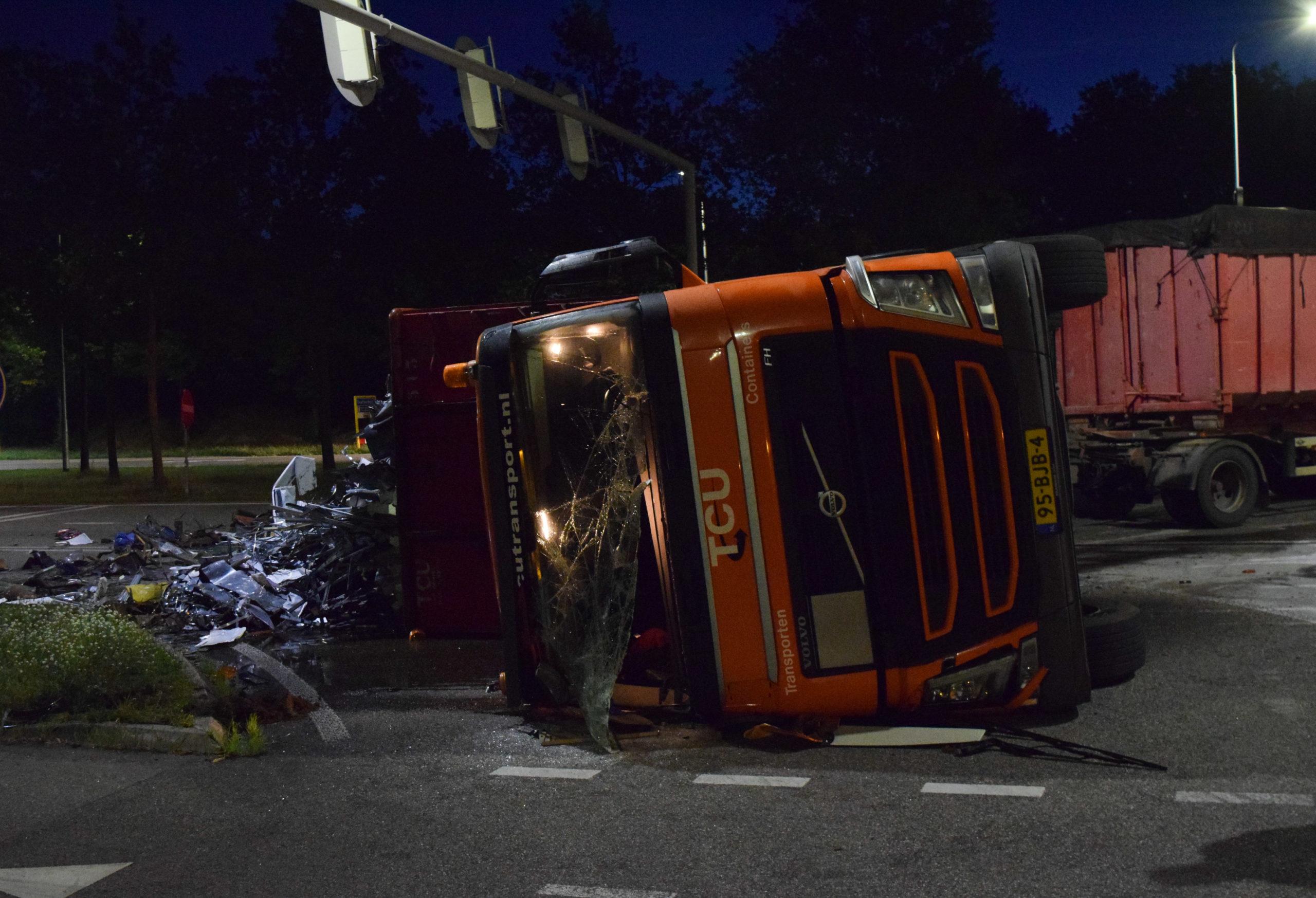 Vrachtwagen kantelt en spreidt zijn lading oud ijzer over de weg uit, verkeerschaos in stad zelf