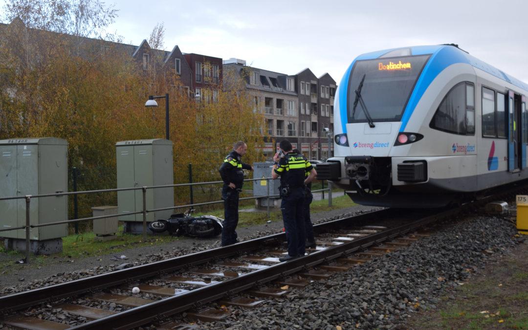 Scooterrijdster komt tegen spoorboom aan en valt, omstander trekt haar weg voor aankomende trein