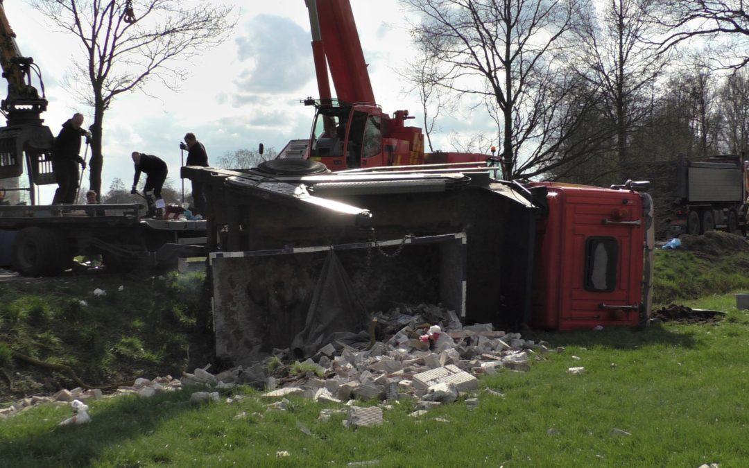 Vrachtwagencombinatie schaart, lading puin en de cabine komen in weiland terecht nabij Westendorp