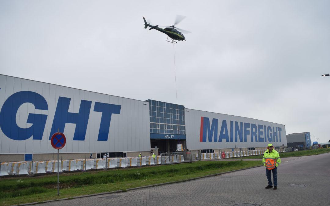 Helikopter ingezet om dakbedekking op dak van bedrijfspand te zetten in 's-Heerenberg.