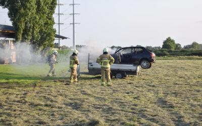 Brand onder motorkap van cross auto op aanhanger